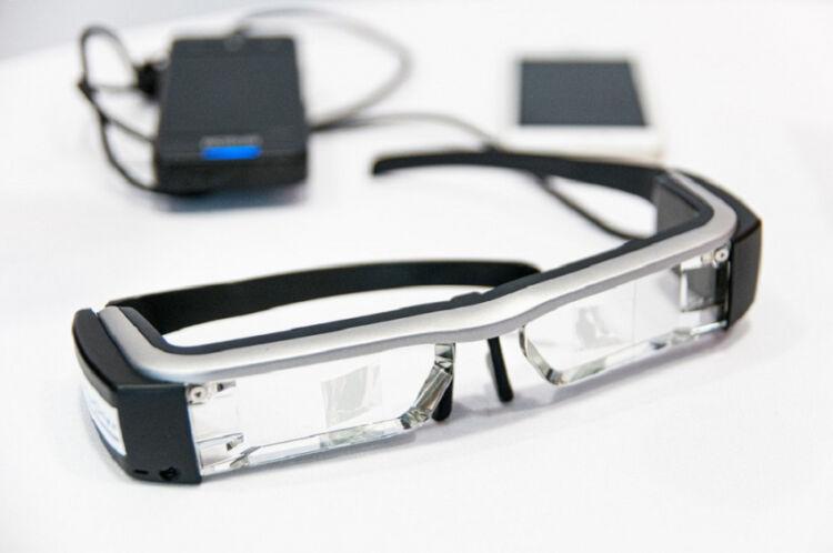 Μέχρι το 2030 τα έξυπνα γυαλιά θα μπορούν να μας «τηλεμεταφέρουν» σε διαφορετικές τοποθεσίες, υπόσχεται ο ιδρυτής του Facebook, Μαρκ Ζούκερμπεργκ. Ένα ζευγάρι προηγμένα «έξυπνα γυαλιά» που θα επιτρέπουν στις προσωπικές συναντήσεις να αντικατασταθούν από μια ψηφιακή εμπειρία, ετοιμάζει το Facebook. Πρόκειται για μια τεχνολογία επαυξημένης πραγματικότητας, η οποία θα παρουσιάζει γραφικά που δημιουργούνται από υπολογιστή σε εικόνες του πραγματικού κόσμου. Σύμφωνα με δηλώσεις του Μαρκ Ζούκερμπεργκ, που έγιναν την περασμένη Δευτέρα, μια τέτοια τεχνολογία όχι μόνο θα περιόριζε την ταλαιπωρία των μετακινήσεων, αλλά θα μείωνε τη ρύπανση που προκαλούν οι μετακινήσεις στο περιβάλλον. «Προφανώς, θα συνεχίσουμε να βρισκόμαστε σε αυτοκίνητα και αεροπλάνα και όλα αυτά. Όμως, όσο περισσότερο μπορούμε να τηλεμεταφερόμαστε, όχι μόνο ελαττώνουμε τις μετακινήσεις αλλά νομίζω ότι κάνουμε καλό στην κοινωνία τον πλανήτη συνολικά», υπογράμμισε ο διευθύνων σύμβουλος του Facebook. Ο ίδιος πιστεύει ότι, μέχρι το 2030, η εταιρεία του θα έχει καταφέρει να κατασκευάσει ένα ζευγάρι γυαλιών με κανονική εμφάνιση, τα οποία μπορούν να δίνουν στο χρήστη την εντύπωση ότι έχει μεταφερθεί πραγματικά σε άλλο χώρο. «Αντί να κάνετε μια βιντεοκλήση, απλά θα κινείτε τα δάχτυλά σας και θα τηλεμεταφέρεστε. Θα νιώθετε ότι είστε στ' αλήθεια στον ίδιο χώρο με τους φίλους σας, θα τους βλέπετε να κάθονται στον καναπέ σαν να ήταν δίπλα σας», είπε ο Ζούκερμπεργκ.